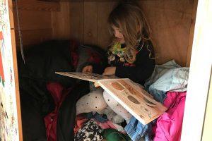 Liv sitzt im Schrank und liest.